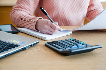 A woman conducts accounting calculations in the office