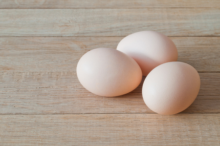 Three eggs on a wooden table