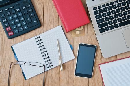 Closeup open notebook, laptop, calculator, pen, smartphone on a wooden table. Business concept
