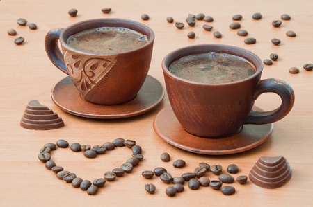 Two cups of coffee with coffee beans in the shape of a heart on a wooden table