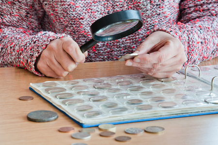 Woman-numismatist views coins from a coin album through a magnifying glass