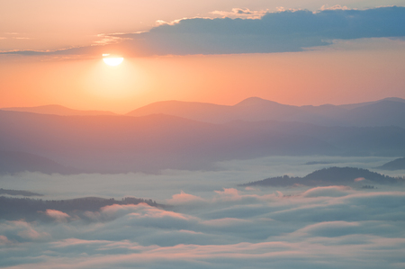 Sunrise over clouds of fog in the mountains.