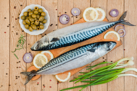 Fresh raw fish mackerel and ingredients for cooking on a wooden background in a rustic style