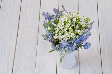 Bouquet of white and blue wild flowers in a cup on a wooden table Stock Photo