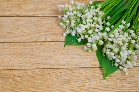 Flowers of the lily of the valley on a wooden table