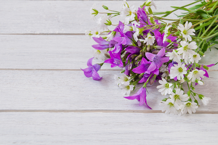 Bouquet of white and purple wildflowers on a white wooden table