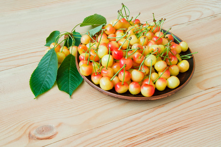 Yellow-red sweet cherry in a plate on a wooden table Stock Photo
