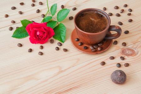A cup of coffee and a red rose on a wooden table Stock Photo