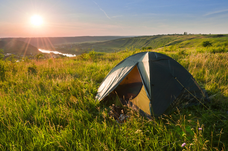 Tourist tent on the high bank of the river at sunset. Beautiful summer landscape Stock Photo