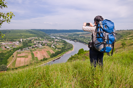 The girl traveler with a tourist backpack photographed a beautiful scenery of the river canyon