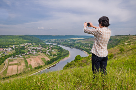 The girl taking pictures the picturesque landscape of the village on the opposite bank from the height of the river canyon