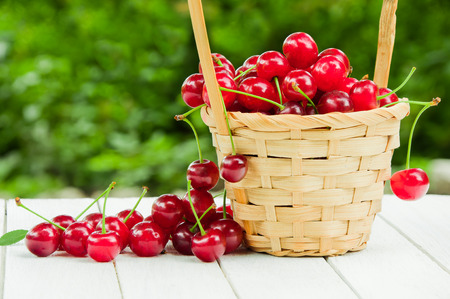 Cherries in a wicker basket on a white wooden table Stock Photo