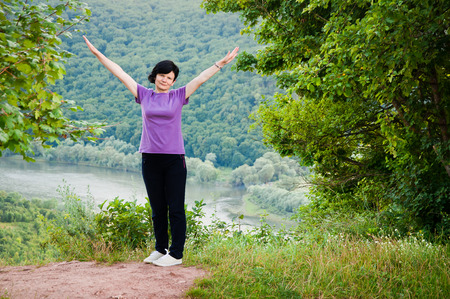 Happy woman with raised hands stands on the bank of the river