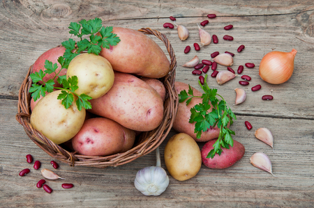 Potatoes in a wicker basket on a wooden table in rustic style