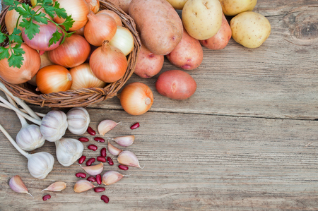 Fresh vegetables on a wooden table: onions, potatoes, garlic Stock Photo
