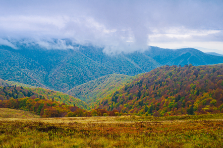 Autumn colors in the background of remote mountains. Clouds fly between the mountains. Autumn mountain landscape