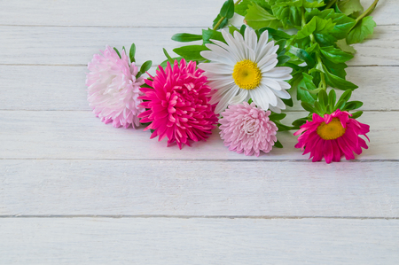 Bouquet of aster on a wooden table background.