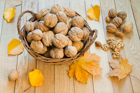 Walnuts in a wicker basket on a wooden table