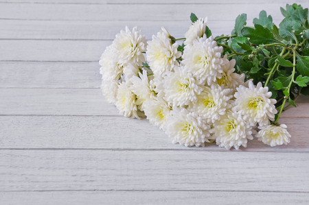Bouquet of white chrysanthemums on a white wooden table