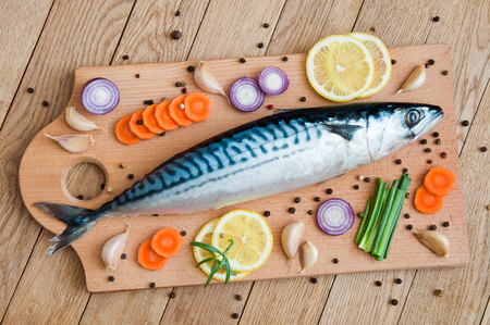 Fresh raw fish mackerel for cooking on a wooden background