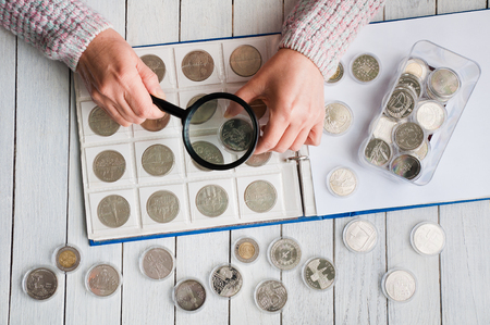 Woman looks at the coins through a magnifying glass