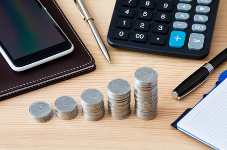Coin columns, calculator, notepad, smartphone and pen on a wooden table Stock Photo