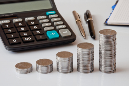 Coin columns, calculator, notepad on white table