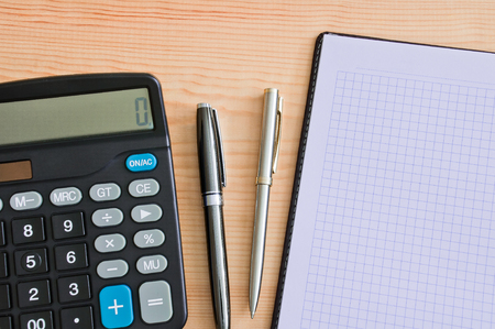 Calculator, two ballpoint pens and a notepad on a wooden table. Copy space