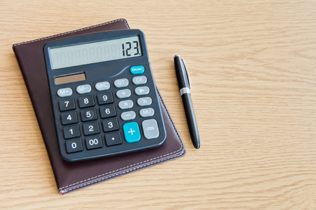 Calculator with a ballpoint pen on a wooden table with Copy Space