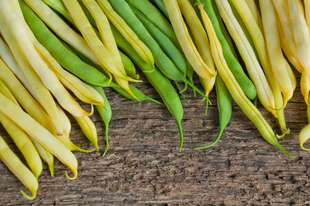 Yellow and green pods of asparagus beans on a wooden table
