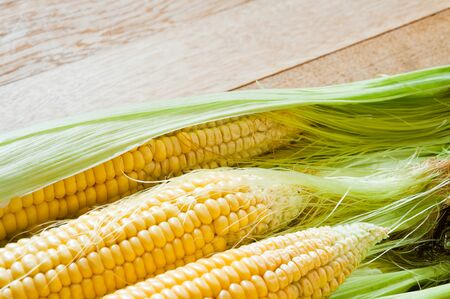 Sweet corn cobs on a wooden table