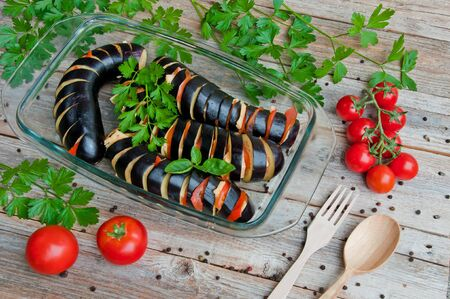 Eggplants sliced for baking with cheese and tomatoes in a transparent bowl Фото со стока