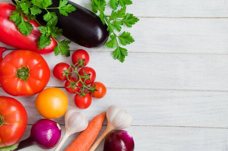 Tomatoes, peppers, eggplants and other vegetables on a white wooden table