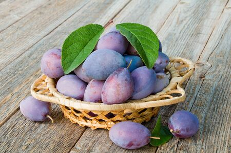 Fresh organic plums in a wicker bowl on a wooden table