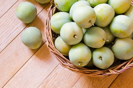 Ripe yellow-green plums in a wicker basket on a wooden table Фото со стока