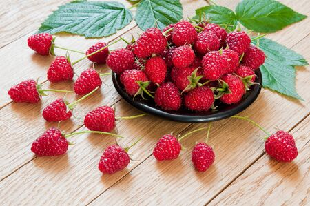 Fresh berries of raspberries on a plate on a wooden table Фото со стока