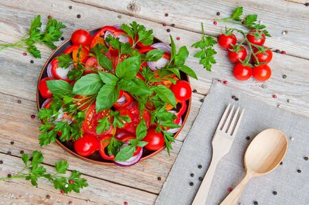 Fresh sliced tomato salad and other vegetables and greens on a plate
