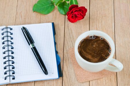 Cup of coffee, notebook with pen and rose on wooden table