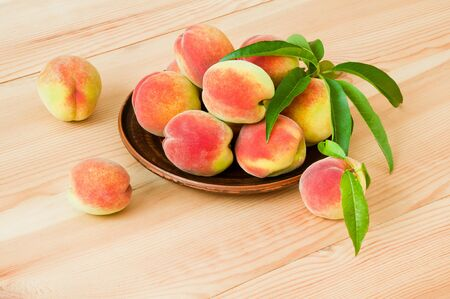 Fresh ripe peaches in a plate on a wooden table