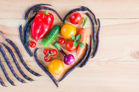 Top view of a heart made from pods of asparagus beans and fresh ripe vegetables on a wooden table