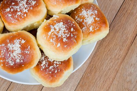Freshly baked buns on a plate on a wooden table