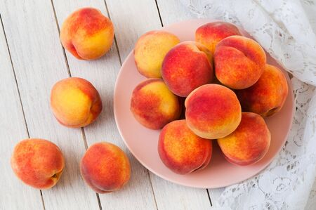 Fresh organic peaches in a plate on a white wooden table Фото со стока