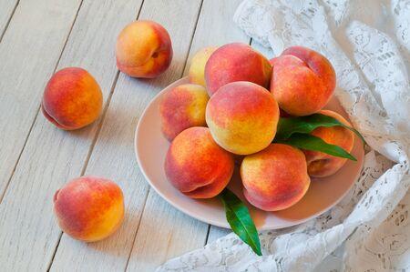Fresh organic peaches in a plate on a white wooden table Archivio Fotografico