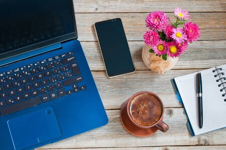 Laptop, notebook with pen, cup of coffee, smartphone and vase with flowers on your desktop