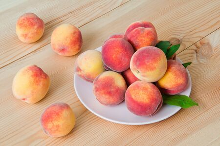 Fresh organic peaches in a plate on a wooden table Фото со стока