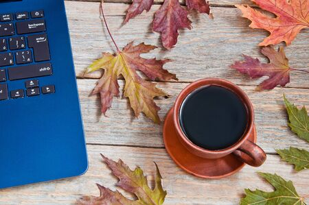 Cup of coffee on the table and laptop computer. Autumn concept