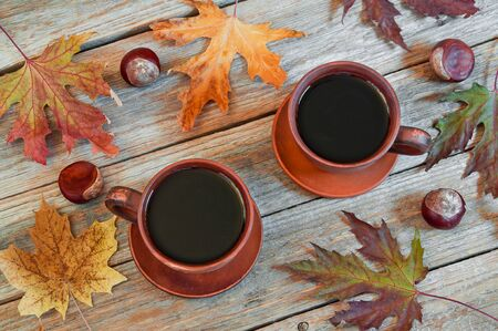 Two cups of coffee on a wooden table. Autumn concept