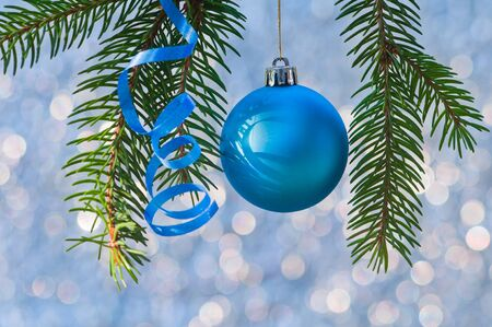Christmas ball, serpentine and branches of fir tree on bokeh background