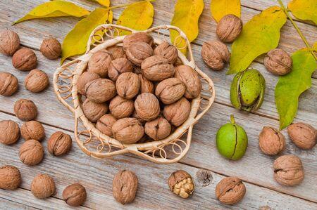 Walnuts in a wicker plate on a wooden table Фото со стока