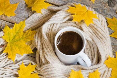 Cup of hot coffee, wrapped in scarf and colorful autumn maple leaves on wooden background